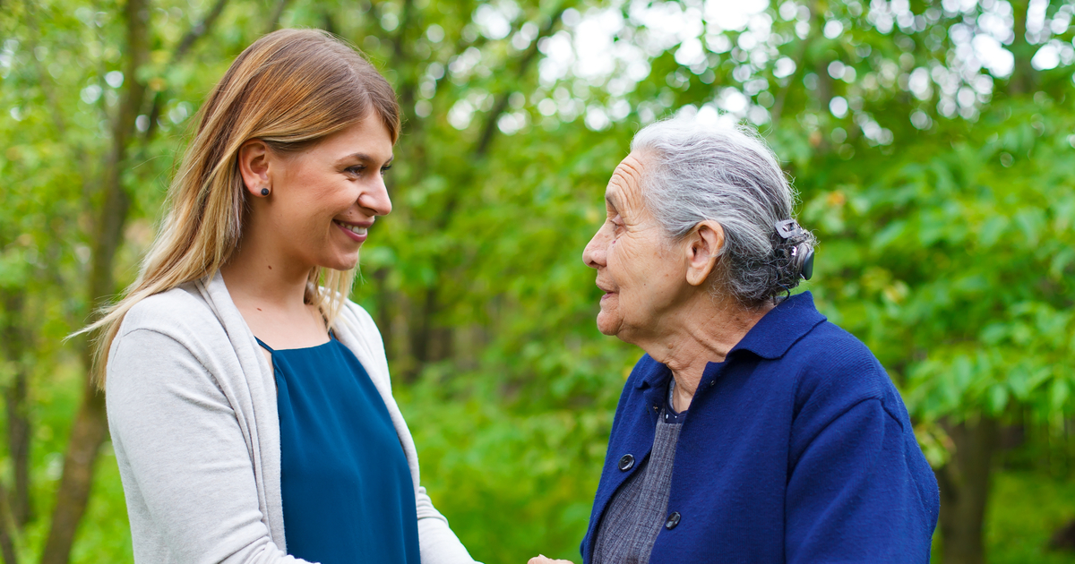 Senior woman outside with caregiver